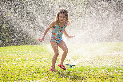 Girl (4-5) splashing in sprinkler water on lawn - p1427m1553590 by Tetra Images