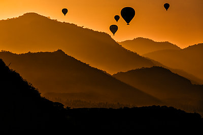 Indonesia, West Nusa Tenggara, Silhouettes of hot air balloons flying over Sumbawa island at moody dusk - p300m2199185 by Konstantin Trubavin