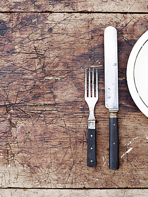 Fork, knife and plate on wooden table, directly above - p528m718714f by Anna Kern