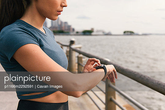 Close up image of jogger checking smart watching before workout - p1166m2292591 by Cavan Images