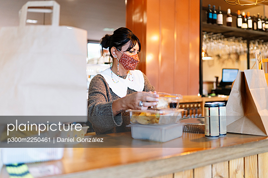 Mature female manager arranging plastic food containers on counter in restaurant during COVID-19 - p300m2250461 by Daniel González