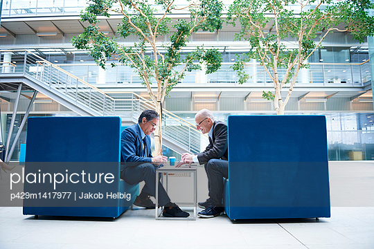 Two businessmen having discussion meeting in office atrium armchairs - p429m1417977 by Jakob Helbig