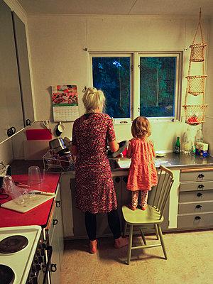 Mädchen mit Großmutter in der Küche - p1418m2008117 von Jan Håkan Dahlström