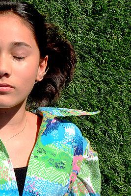 Girl lying in grass - p1521m2065471 by Charlotte Zobel