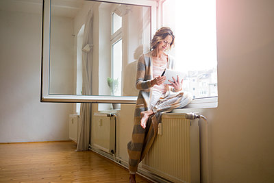 Mature woman in empty room using tablet at the window - p300m1562480 by Robijn Page