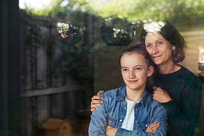 Smiling woman and daughter looking through window while standing at home - p300m2197412 by Stefanie Aumiller