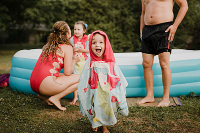 Happy girl wrapped in a funny towel at an inflatable swimming pool in garden - p300m2206978 by Sara Monika