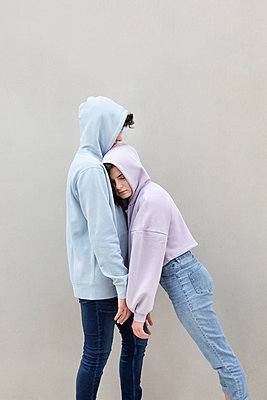Teenage girl leaning on boyfriend by wall - p300m2277437 by Petra Stockhausen