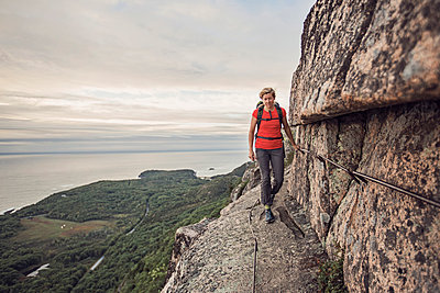 Woman hiking along cliff edge, Acadia National Park, Maine, USA - p343m1569053 by Chris Bennett