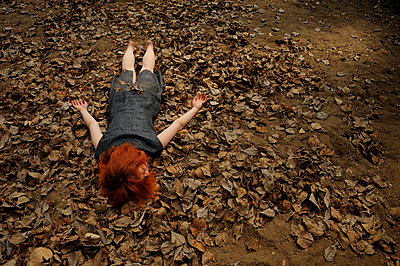 Red-haired woman lying on autumn leaves - p491m1132548 by Ernesto Timor