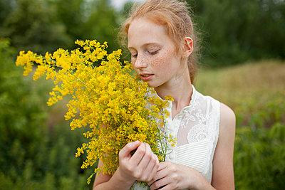 Caucasian girl smelling wildflowers - p555m1521404 by Vyacheslav Chistyakov