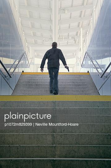 Man walking up steps holding a gun - p1072m829399 by Neville Mountford-Hoare