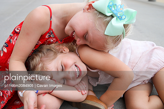 little girls laughing snuggled together on boardwalk holding hands - p1166m2084905 by Cavan Images
