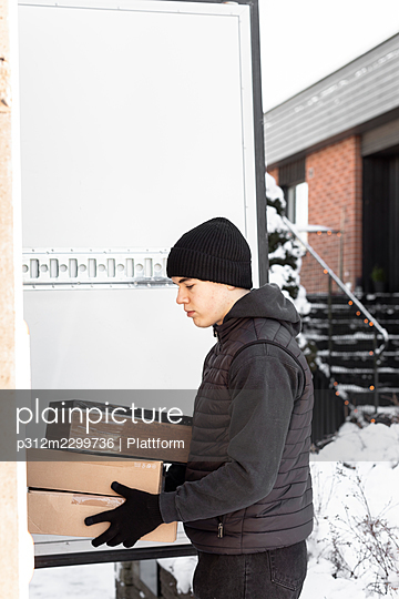 Man unloading parcels from car trunk - p312m2299736 by Plattform