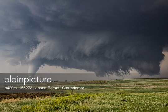 Three tornadoes touch down simultaneously.  A large cone tornado is on the left.  Two very fine vortices descend from the ragged wall cloud on the right - p429m1156272 by Jason Persoff Stormdoctor