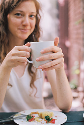 Smiling woman holding a white china teacup. - p1100m1080261 by Mint Images