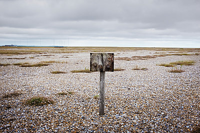 Old weathered wooden sign on pebble beach. - p1100m1490128 by Mint Images