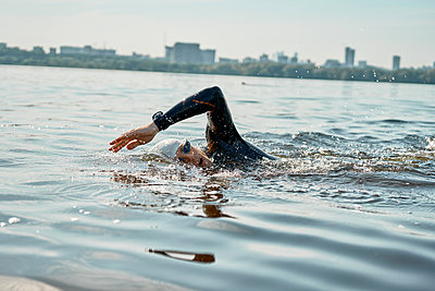 Young man in swimming suit training in river - p1630m2197078 by Sergey Mironov