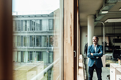 Contemplating businessman with arms crossed looking through window while standing in office - p300m2266295 by Gustafsson