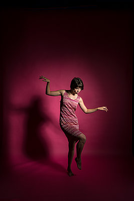 Young woman makes dancing steps - p427m1516019 by Ralf Mohr