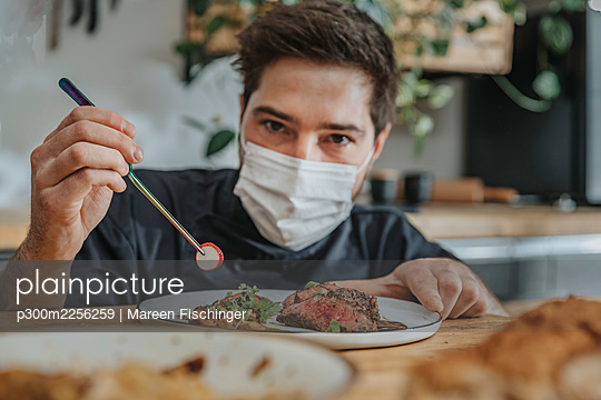 Male chef wearing protective face mask garnishing vegetable on tomahawk steak while working in kitchen - p300m2256259 by Mareen Fischinger