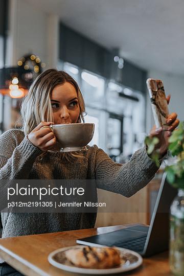 Woman taking selfie in cafe - p312m2191305 by Jennifer Nilsson