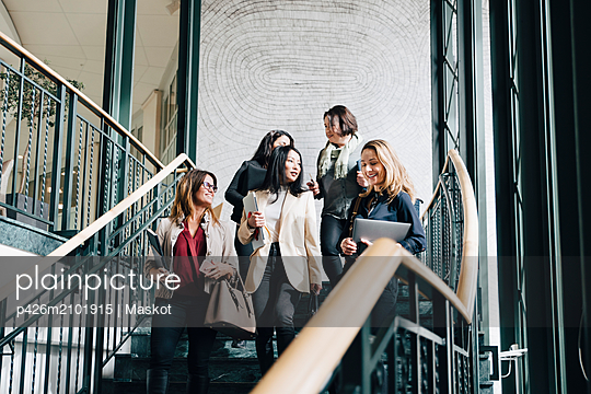 Low angle view of smiling female entrepreneurs moving down on staircase in office - p426m2101915 by Maskot