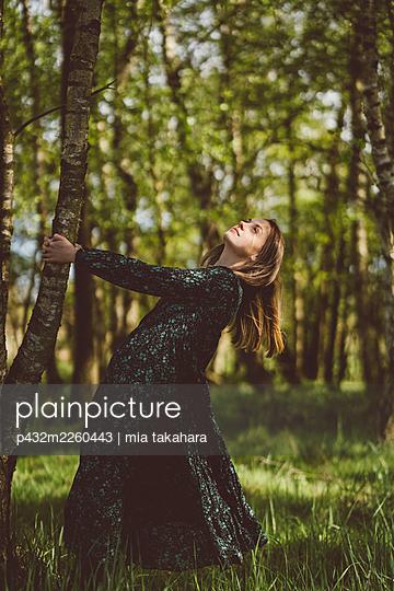 Junge Frau steht verträumt an einem Baum - p432m2260443 von mia takahara