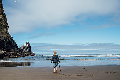 Rear view of boy holding stick while walking on sand at beach against sky - p1166m1524546 by Cavan Images