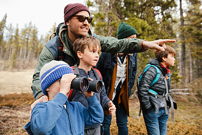Family with binoculars bird watching, hiking in woods - p1192m2094192 by Hero Images