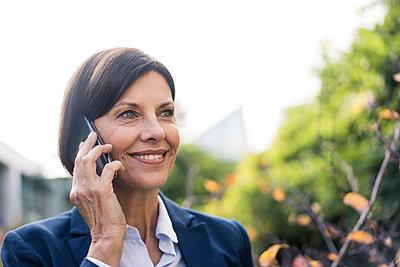 Smiling female entrepreneur talking on mobile phone at office park - p300m2266635 by Joseffson