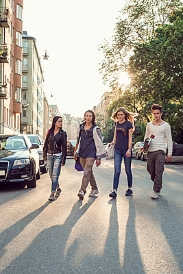 Full length of confident high school students walking on city street - p426m958671f by Maskot