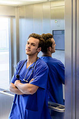 Young male junior doctor in hospital elevator, portrait - p429m2097547 by suedhang photography