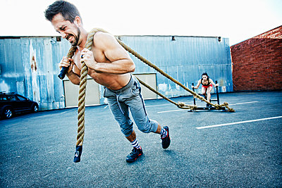 Caucasian man pulling woman with heavy ropes in parking lot outdoors - p555m1304122 by Peathegee Inc