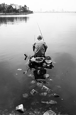 A Vietnamese man sits on his fishing plinth in West Lake - p934m892998 by William Brantingham photography