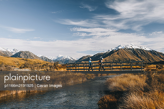 Couple of young hikers crossing a creek, Lake Clearwater, New Zealand - p1166m2191925 by Cavan Images