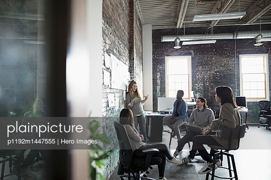 Creative business people brainstorming at brick wall in open plan loft office