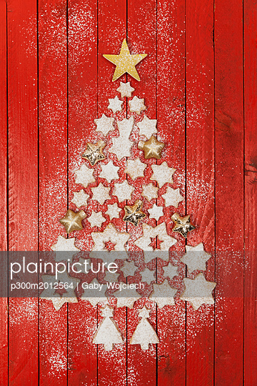 Christmas cookies and star-shaped Christmas baubles forming Christmas tree on red wooden background - p300m2012564 von Gaby Wojciech