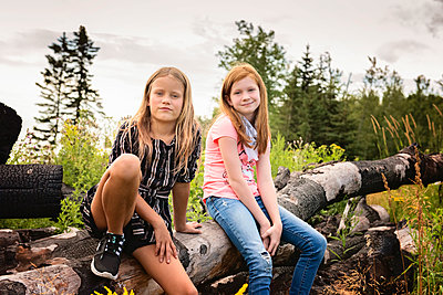Two Young Girls Sitting on a Log - p1166m2207810 by Cavan Images