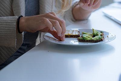 Junge Frau isst Butterbrote - p1212m1201683 von harry + lidy