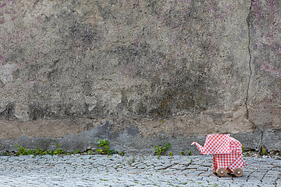 Origami elephant on cobblestones, concrete wall - p300m2012952 von Petra Stockhausen