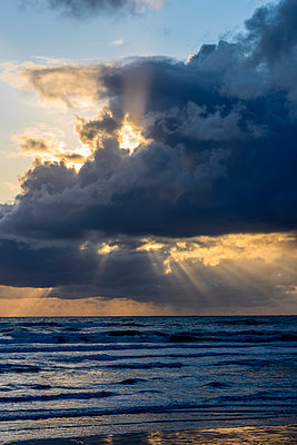 Sunbeams flow through holes in the clouds along the Oregon Coast; Cannon Beach, Oregon, United States of America - p442m1449212 by Robert L. Potts