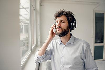 Man listening to music with headphones - p586m1562038 by Kniel Synnatzschke