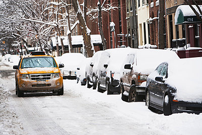 Taxi driving on snowy city street - p924m807186f by Ditto