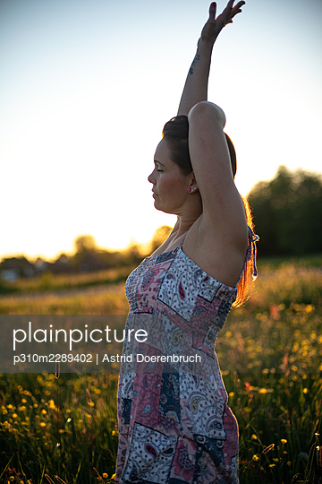Woman stretching in the meadow - p310m2289402 by Astrid Doerenbruch
