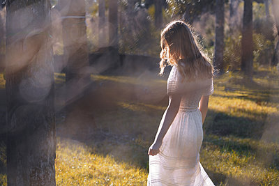 Back view of a red-haired young woman in a delicate dress walking in the sunny forest  - p1694m2291698 by Oksana Wagner