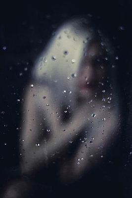 Woman behind windowpane - p916m952788 by the Glint