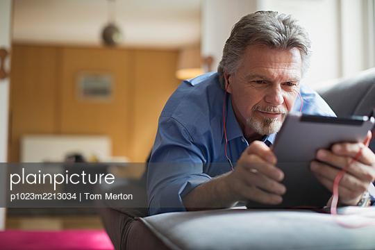 Senior man using headphones and digital tablet on living room sofa - p1023m2213034 by Tom Merton