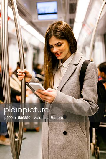 Spain, Barcelona, young businesswoman using cell phone in underground train - p300m1586980 von Valentina Barreto