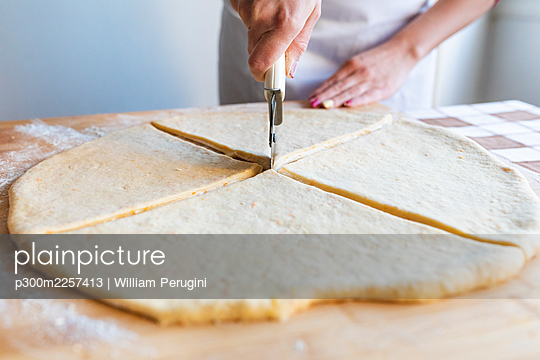 Woman cutting dough slices with pizza cutter in kitchen - p300m2257413 by William Perugini